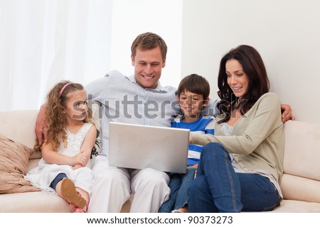 Young family surfing the internet together - stock photo