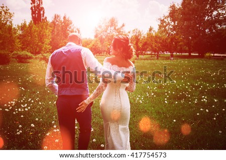 young family. the bride and groom are going to meet his future, his happiness, tenderly embracing each other at sunset. - stock photo