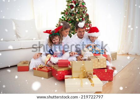 Young family unpacking Christmas presents against snow falling - stock photo