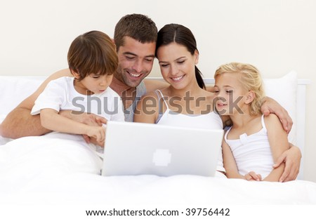 Young family using a laptop in bed - stock photo