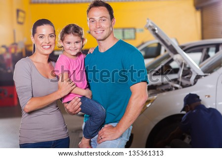 young family waiting in garage while their car serviced - stock photo