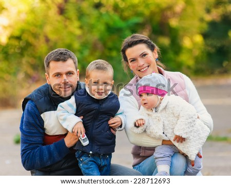 Young family walking in the park. Autumn. - stock photo