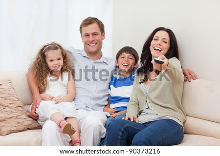 Young family watching comedy together - stock photo