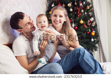 Young family with a baby having fun on bed at home with Christmas tree in the background  - stock photo