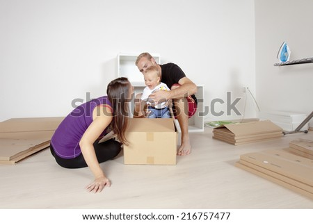 Young Family with a Baby  Moving in a New Apartment - stock photo