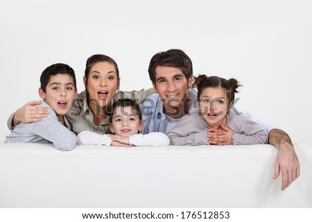 Young family with a board left blank for your message - stock photo