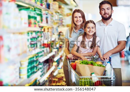 Young family with a cart in the store - stock photo