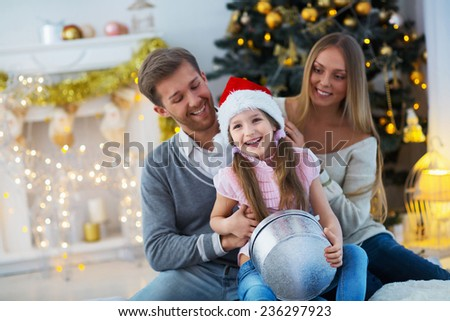 Young family with a gift at home - stock photo