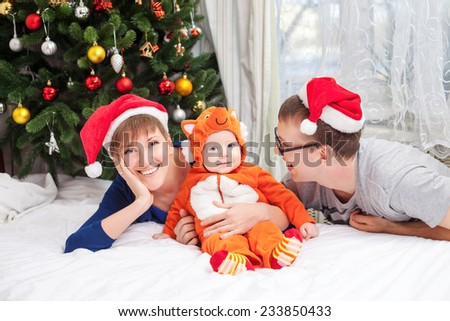 Young family with baby boy dressed in fox costume - stock photo