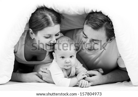 Young family with baby boy under blanket on bed at home - stock photo