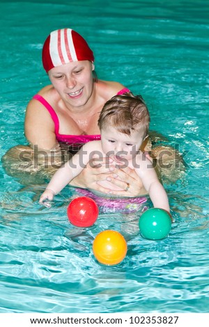 Young family with baby having fun in the swimming pool - stock photo