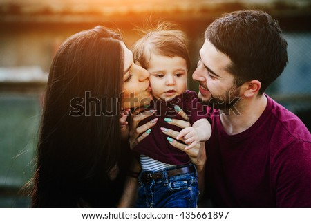 Young family with child posing on the background of an abandoned building - stock photo