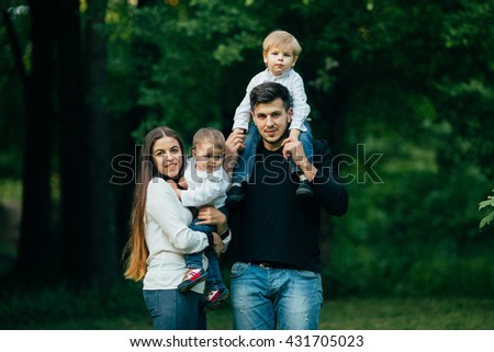 Young family with children, Happy father, mother and two sons spending time in park. - stock photo