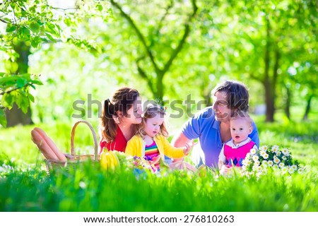 Young family with kids having picnic outdoors. Parents with two children relax in a sunny summer garden. Mother, father, little girl and baby boy eat sandwich and fruit, drink juice for lunch in park - stock photo