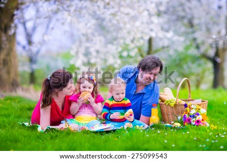 Young family with kids having picnic outdoors. Parents with two children relax in blooming summer garden. Mother, father, little girl and baby boy eat sandwich and fruit, drink juice for healthy lunch - stock photo