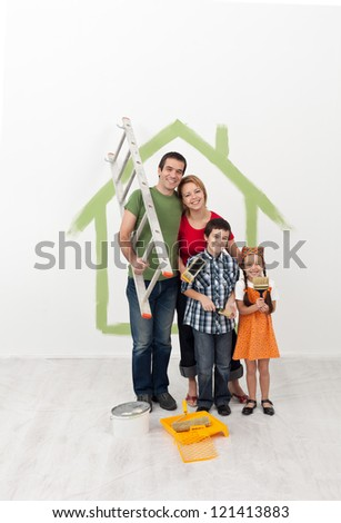 Young family with kids redecorating their home - holding painting utensils and smiling - stock photo