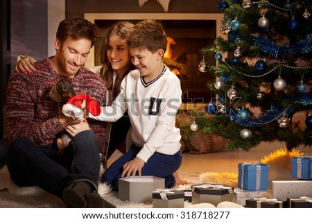 Young family with little boy holding puppy received for christmas. - stock photo