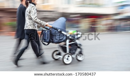 Young family with small children and a pram walking down the street. Intentional motion blur - stock photo