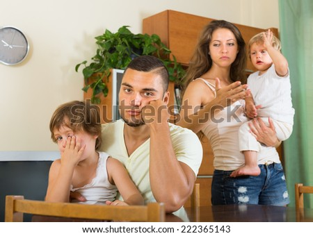 Young family with two children on hands having quarrel in home interior  - stock photo