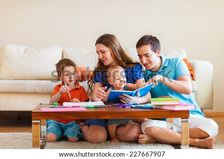 Young family with two kids drawing and reading together - stock photo
