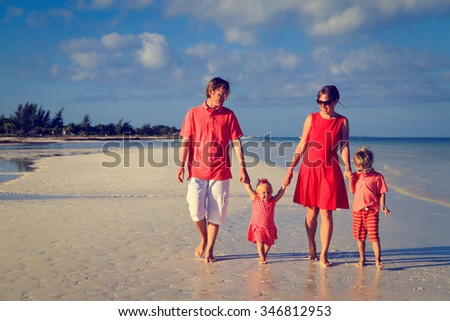 Young family with two kids walking at sand beach - stock photo