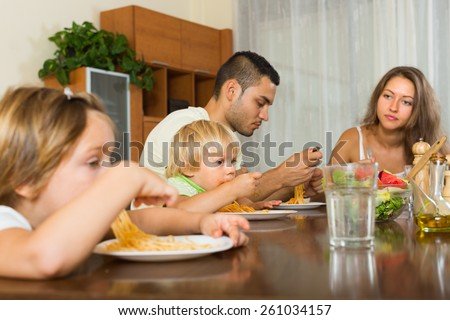 Young family with two little children eating with spaghetti at table. Focus on girl - stock photo