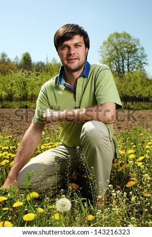 Young farmer knelt near his land in a sunny day - stock photo