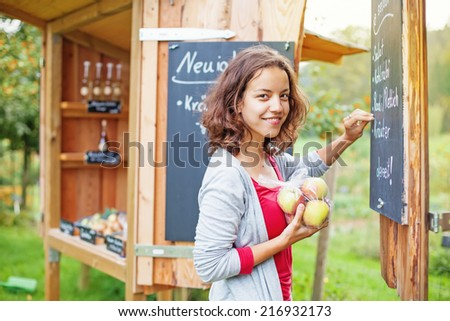 Young farmer making advertising for her little shop - stock photo