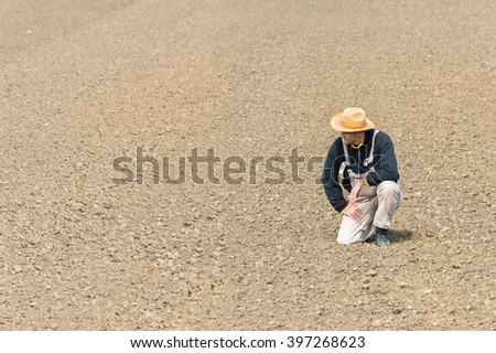 young farmer watching plowed field - stock photo