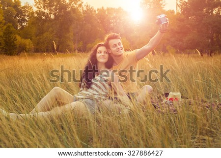 young fashion beautiful loving casual style couple lying down on floral field in autumnal park, warm sunny day, enjoying family, romantic date, happiness and love concept. making selfie with camera. - stock photo