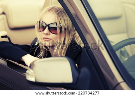 Young fashion blond woman in a convertible car  - stock photo