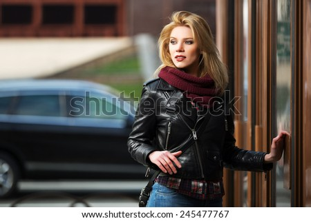 Young fashion blond woman in leather jacket at the mall door - stock photo