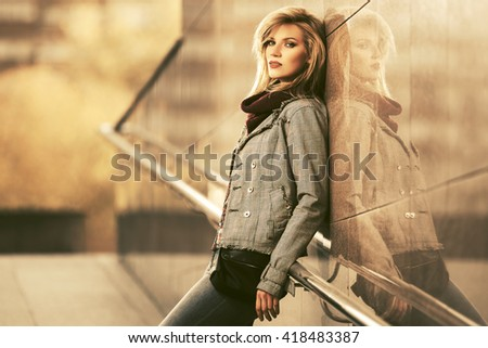 Young fashion blond woman standing at the wall. Female stylish model outdoor - stock photo