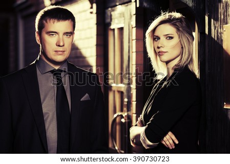 Young fashion business couple against office building - stock photo