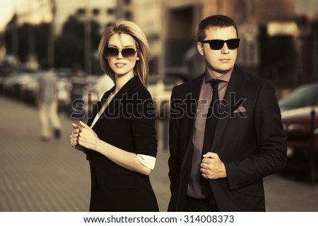 Young fashion business couple walking on the city street - stock photo