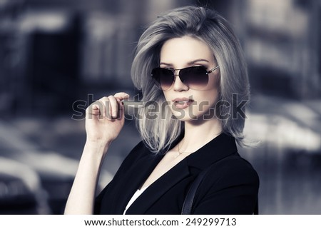 Young fashion business woman in sunglasses on a city street - stock photo