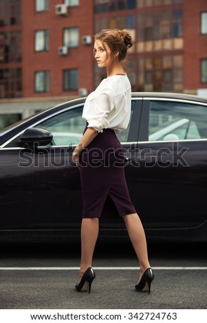 Young fashion business woman on the city street next to her car - stock photo