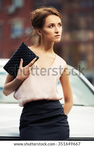 Young fashion business woman with handbag standing beside her car - stock photo