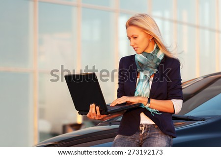 Young fashion business woman with laptop by her car - stock photo