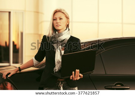 Young fashion business woman with laptop standing by her car - stock photo