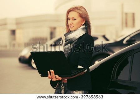 Young fashion business woman with laptop standing next to her car - stock photo