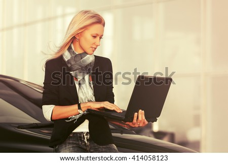 Young fashion business woman with laptop standing next to her car. Female blond fashion model in black jacket outdoor - stock photo
