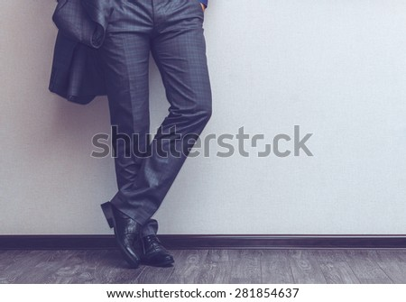 Young fashion businessman's legs in classic suit and shoes on wooden floor - stock photo