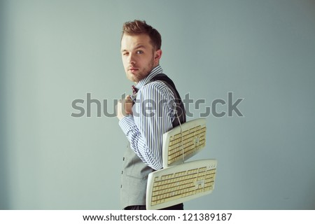 Young fashion computer geek with beard in suit carrying keyboards underhand - stock photo