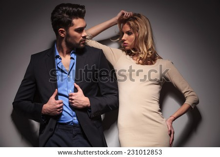 Young fashion couple looking at each other, the woman is fixing her hair while the man is fixing his jacket, both looking away. - stock photo