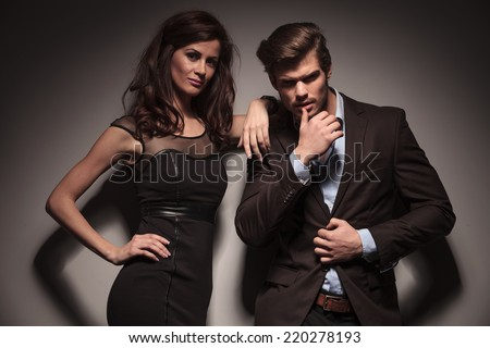 Young fashion couple looking into the camera while the man is pulling his jacket with one hand and touching his lip with his thumb. The woman is leaning on him. On dark grey background. - stock photo