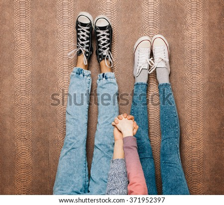 Young fashion couple's legs in jeans and sneakers feet up and holding hands on the wall. Close up - stock photo