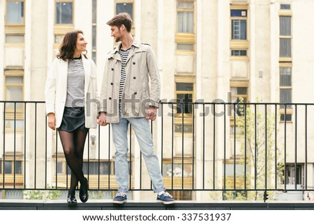 Young fashion couple walking down the street in summer near skyscraper. Pretty beautiful woman in stripes  clothes.  - stock photo