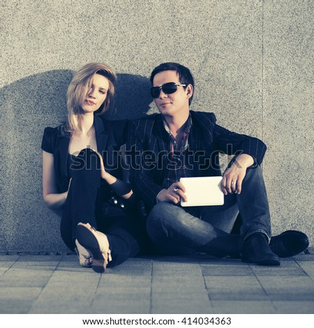 Young fashion couple with tablet computer sitting at the wall. Male and female stylish model. Man and woman outdoor - stock photo