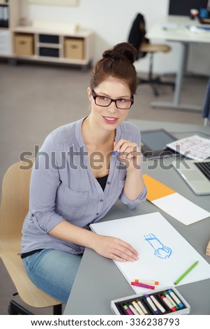 Young fashion designer wearing eyeglasses sitting at a table in her studio working on a sketch with colorful wax crayons, high angle view - stock photo